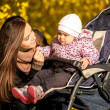 Young mother talking with little daughter in pram — Stock Photo