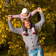 Man playing with daughter at autumn park — Stock Photo