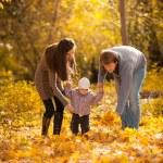 Parents teaching small daughter to walk at autumn park — Stock Photo #42918075
