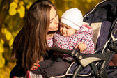 Portrait of mother kissing daughter in buggy — Stock Photo