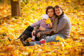 Happy family sitting on leaves at autumn park — Stock Photo