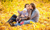Family sitting on leaves at autumn park — Stock Photo