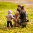 Girl playing with teddy bear and parents at park — Stok fotoğraf