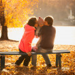 Family sitting with small daughter on bench at lake — Stock Photo