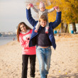 Young family having fun on beach at autumn — Stock Photo