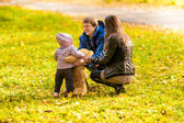 Family playing with daughter and teddy bear at park — Stock Photo