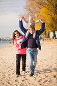 Young family having fun on beach at autumn — Stock Photo