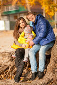 Family with small daughter sitting under tree — Stock Photo