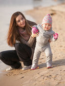 Brunette mom helping small daughter to walk on beach — Stock Photo