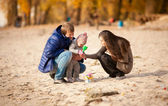 Family playing on beach with daughter at autumn — Stock Photo
