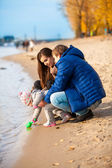 Daughter digging sand with shovel on beach with parents — Stock Photo