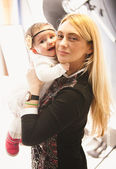 Aged blonde woman holding baby girl on hands — Stock Photo