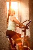 Smiling woman riding exercise bike at gym — Stock Photo