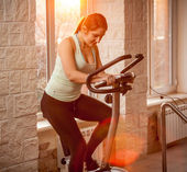 Beautiful woman on exercise bike at gym — Stock Photo