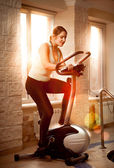 Photo of woman riding trainer bike at fitness club — Stock Photo