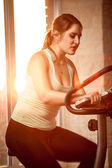 Sexy brunette woman riding on exercise bike — Stock Photo
