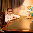 Girl in eyeglasses sitting behind table at cabinet — Stock Photo
