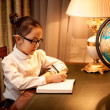 Girl writing in notebook at desk with lamp and globe — Stock Photo
