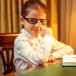 Young girl in eyeglasses sitting behind desk — Stock Photo #43227559