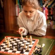 Girl making move on chess board — Stock Photo