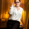 Businesswoman in eyeglasses and white blouse sitting on table — Stock Photo