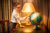Young schoolgirl studying globe at desk — Stock Photo