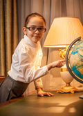 маленькая девочка в очки, указывая на глобус — Стоковое фото
