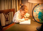 Little girl doing geography homework — 图库照片