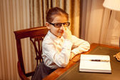 Girl in eyeglasses sitting behind table with notebook — ストック写真