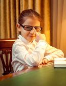 Young girl in eyeglasses sitting behind desk — Stock Photo