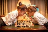 маленькая сестра играть в шахматы и, глядя глаза в глаза — Стоковое фото