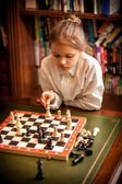 Girl making move on chess board — Stockfoto
