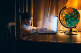 Little girl doing homework on laptop at evening — Stock Photo