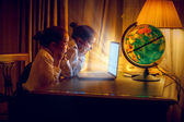 Girls looking with amazement at laptop at night — Stock Photo