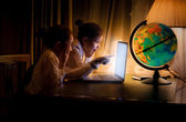 Little sisters using laptop at night — Stok fotoğraf
