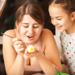 Portrait of mother and girl painting easter eggs — Stock Photo #43325959