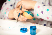 Shot of girl holding brush and painting ester egg — Stock Photo
