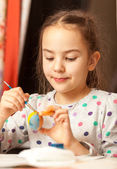 Girl painting traditional easter eggs at home — Stock Photo