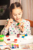 Photo of little diligent girl painting easter egg — Stock Photo