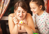 Portrait of mother and girl painting easter eggs — Stock Photo
