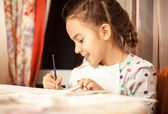 Diligent girl doing drawings with brush — Stock Photo