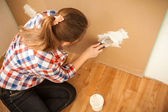 Woman plastering wall at house — Stockfoto