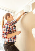 Portrait of young woman aligning gypsum cardboard — Stock Photo