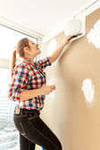 Female painter plastering gypsum cardboard wall — Stock Photo
