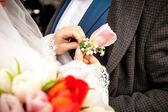 Bride adjusting boutonniere on grooms jacket — Stock Photo