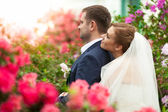 Bride holding groom from back among flower — Foto de Stock