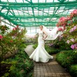 Bride in dress with long veil standing on path at greenhouse — Stock Photo #43481605