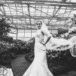 Sexy bride with long veil standing at orangery — Stock Photo #43481613