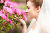 Portret van mooie bruid bruid ruikende bloemen in het park — Stockfoto