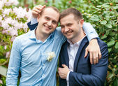 Embracing groom and friend at park — Stock Photo